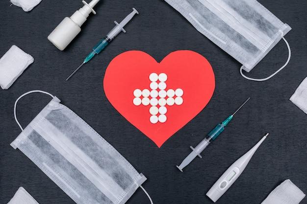 Forma de corazón con icono de cruz en el interior formado por pastillas con agujas, termómetro, spray nasal y máscaras