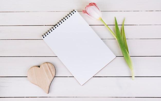 Forma de corazón de madera; bloc de notas de espiral en blanco y tulipán en mesa de madera