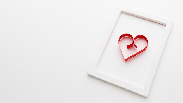 Forma de corazón de papel en marco con espacio de copia