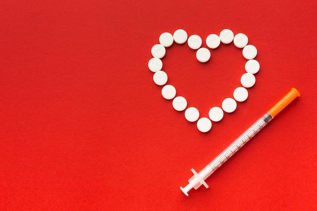 Forma de corazón de pastillas y jeringas