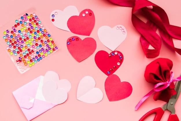 Forma de corazón rojo con cintas sobre fondo rosa
