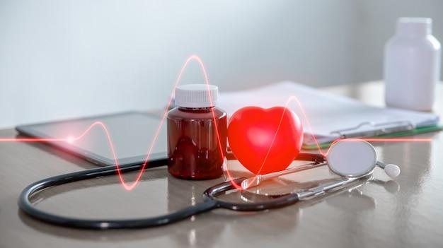 Forma de corazón rojo colocado con botella de médico y un estetoscopio en la mesa del médico.