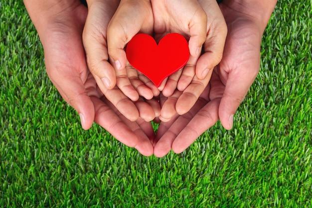 Forma de corazón rojo en manos de miembros de la familia sosteniendo