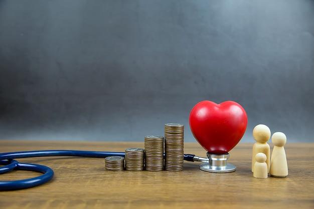 La forma del corazón rojo y las monedas se apilan en forma de gráfico. y estetoscopio médico el concepto de examen físico y seguro de salud.