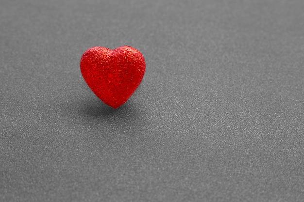 La forma de corazón rojo sobre fondo gris oscuro brillo en concepto de amor para el día de san valentín