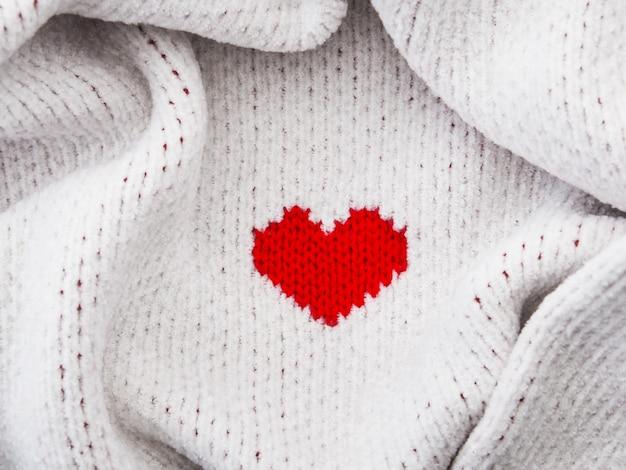 En forma de corazón rojo sobre la textura de la tela blanca. fondo del concepto de día de san valentín.