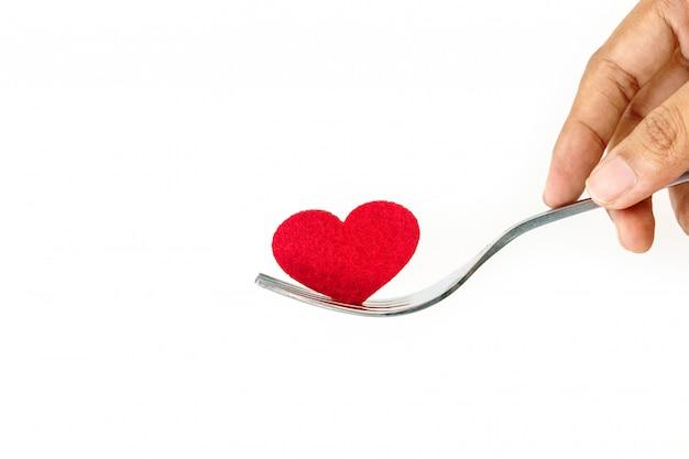 La forma de corazón rojo en tenedor de plata.