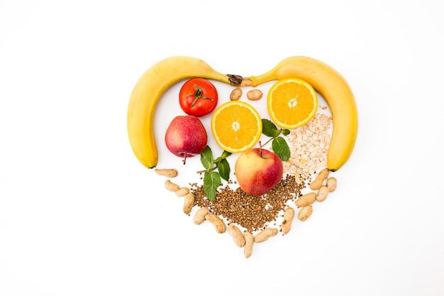 En forma de corazón por varias verduras y frutas.