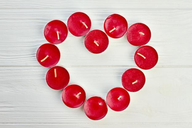 Forma de corazón de velas ligeras de té rojo. velas rojas formando forma de corazón sobre fondo de madera clara, vista superior. concepto de amor y romance.