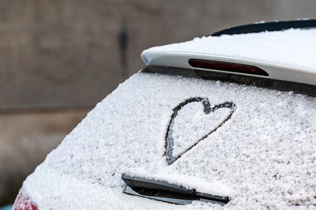 En forma de corazón en la ventana trasera del automóvil cubierto de nieve
