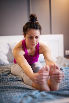 Forma deportiva mujer de mediana edad estirando ejercicio de yoga mientras se sienta hacia adelante en la cama mientras sus manos sostienen los pies.