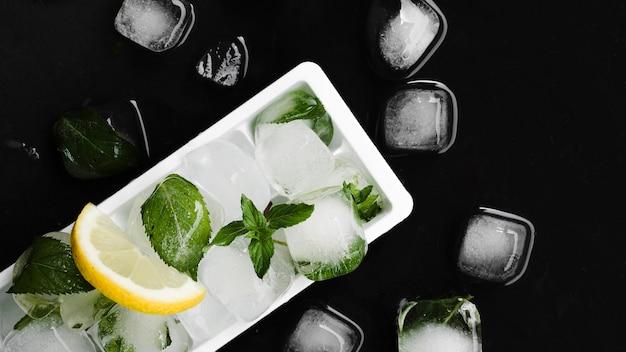 Forma para hielo, cubitos de hielo y rodaja de limón.