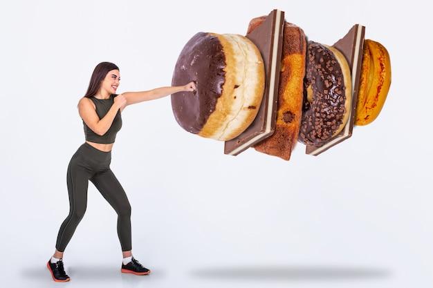 Forma joven diciendo no a los dulces, dulces y carbohidratos