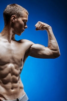 Forma joven con hermoso torso en la pared azul