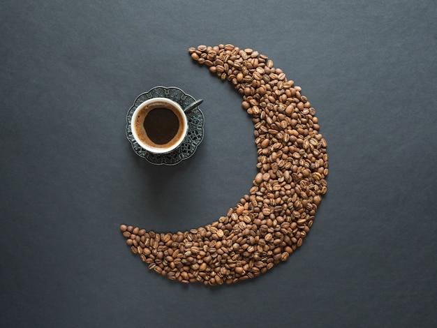 Forma de media luna hecha de granos de café y una taza de café negro sobre la mesa negra. vista superior.