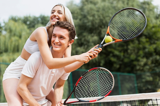Forma pareja joven jugando tenis