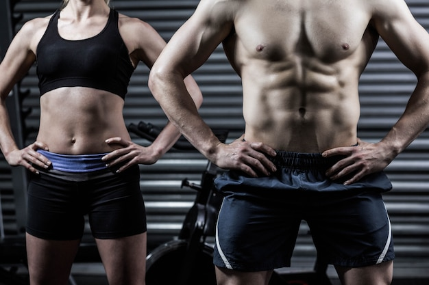 Forma pareja con las manos en las caderas en el gimnasio