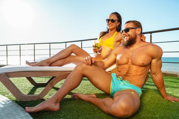 Forma pareja muscular en traje de baño relajante cerca de la piscina