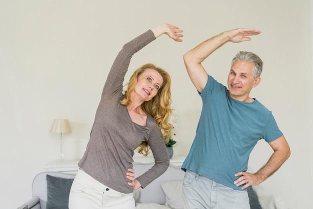 Forma pareja senior haciendo ejercicio en interiores