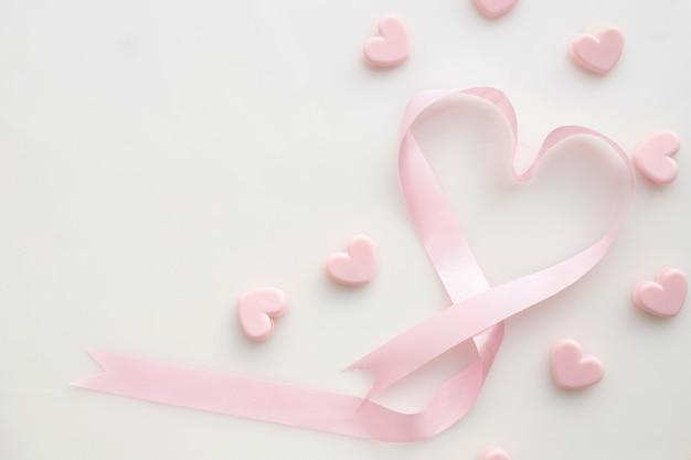 Forma rosada del corazón de la cinta en fondo blanco aislado