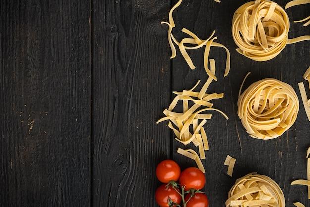 Forma de tallarines enrollados de pasta italiana con conjunto de ingredientes, sobre mesa de madera negra, vista superior plana