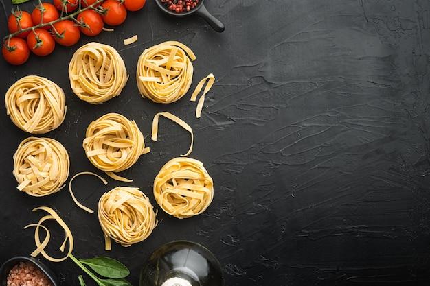 Forma de tallarines enrollados de pasta italiana con ingredientes, sobre mesa de piedra negra, vista superior plana