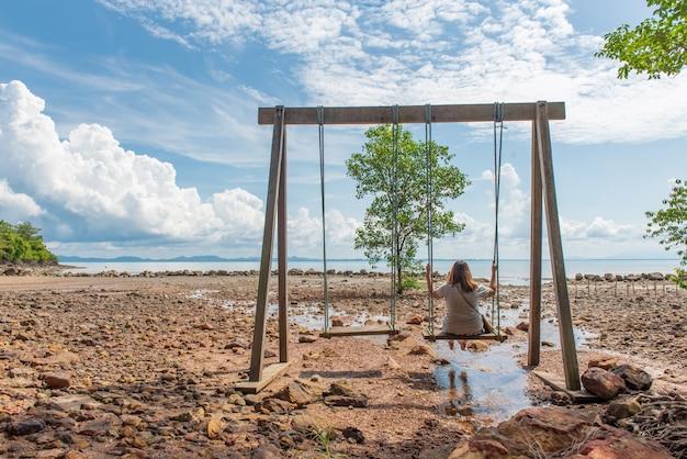 Forma de vida de una niña feliz en el columpio en la playa de mar en una isla tropical, viajando y relajándose el concepto.