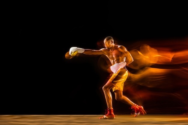 Formación de boxeador profesional aislado sobre fondo negro de estudio en luz mixta
