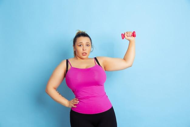 Formación de jóvenes caucásicos plus size modelo femenino sobre fondo azul. concepto de deporte, emociones humanas, expresión, estilo de vida saludable, cuerpo positivo, igualdad. entrenando con las pesas, copyspace.