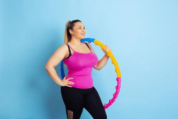 Formación de jóvenes caucásicos plus size modelo femenino sobre fondo azul. concepto de deporte, emociones humanas, expresión, estilo de vida saludable, cuerpo positivo, igualdad. haciendo ejercicio, posando con el aro.