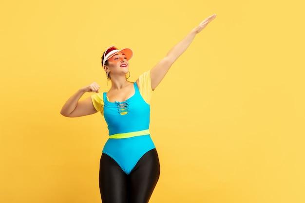 Formación modelo de mujer joven en la pared amarilla