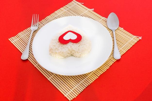 Formas de corazón de arroz cocido con una cuchara y un tenedor en un plato blanco