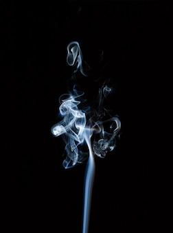 Formas extrañas de humo de incienso en un fondo negro.