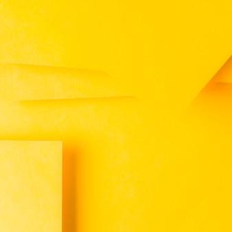 Formas geométricas mínimas y líneas sobre papel amarillo.