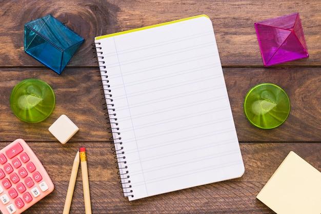Formas geométricas y papelería alrededor del cuaderno