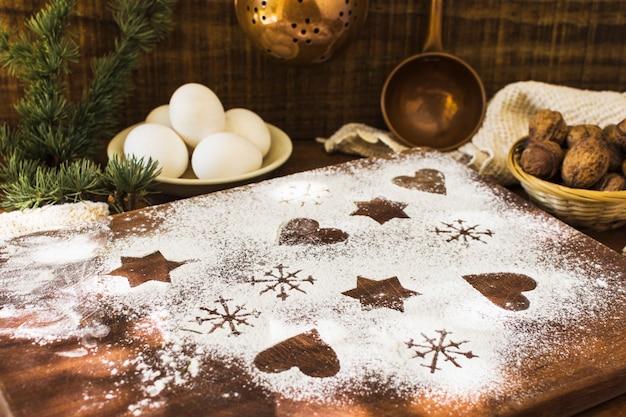 Formas en harina cerca de ingredientes y ramita de coníferas