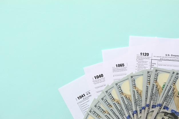 Las formas de impuestos se encuentran cerca de cien billetes de dólar y una pluma azul sobre un fondo azul claro. declaración de impuestos
