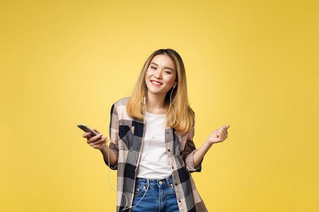 Forme a la mujer asiática sonriente que escucha la música en auriculares sobre fondo amarillo.