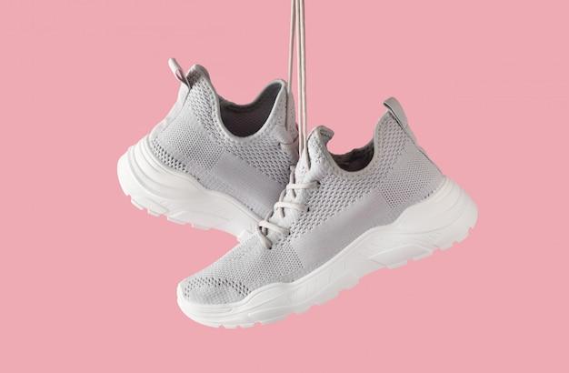 Forme los zapatos deportivos femeninos elegantes para la ejecución cuelgue en fondo rosado. zapatillas grises de textil con suela blanca. cerrar con espacio de copia