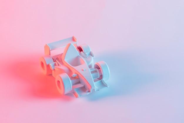 Fórmula miniatura pintada de un coche sobre fondo rosa.