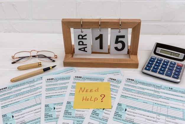 Formulario 1040 con calendario de madera, calculadora y pegatina