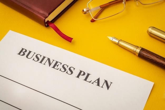 Formulario en blanco, gafas y bolígrafo para elaborar el plan de negocios en la mesa amarilla