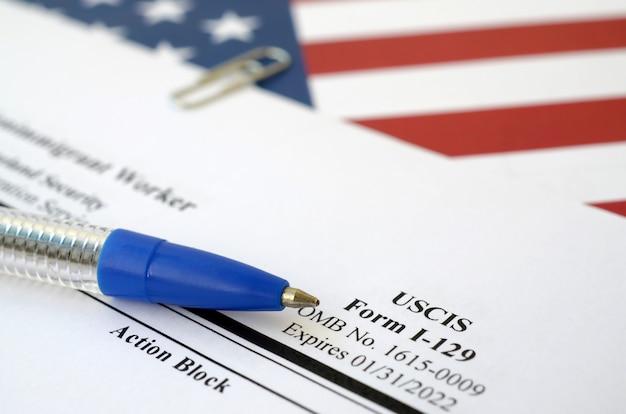 El formulario en blanco i-129 petición para un trabajador no inmigrante se encuentra en la bandera de los estados unidos con un bolígrafo azul del departamento de seguridad nacional