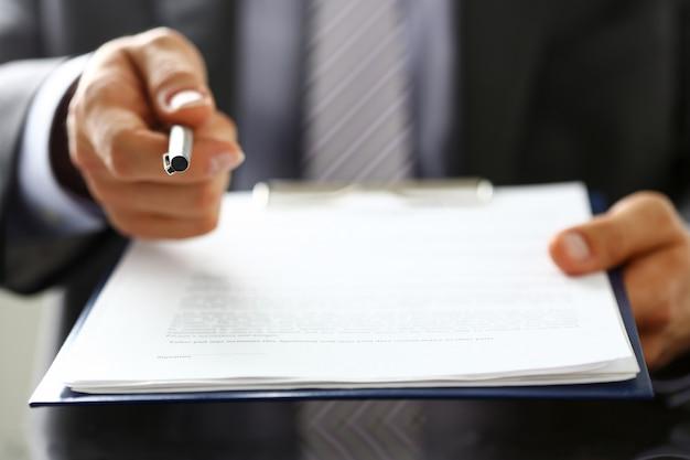 Formulario de contrato de oferta de brazo masculino en traje en portapapeles