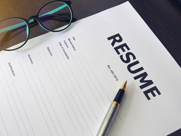 Formulario de currículum vitae con bolígrafos y gafas.