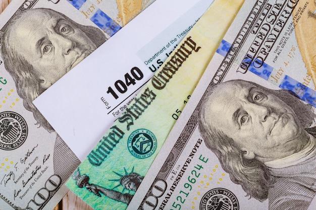 Formulario de impuestos 1040 con cheque de reembolso y primer plano de billetes en dólares estadounidenses