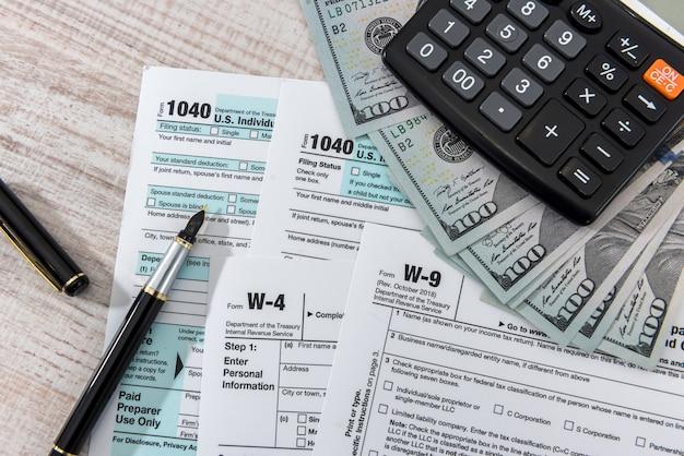 Formulario de impuestos 1040 en el escritorio con calculadora de lápiz y dólar estadounidense. concepto de negocio.