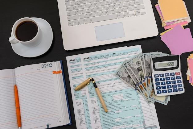 Formulario de impuestos 1040 con laptop y café en la oficina