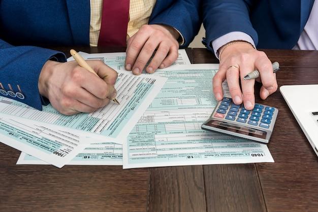 Formulario de impuestos de documento de finanzas contables y llenado de hombre 1040 con calcualtor. hora de impuestos