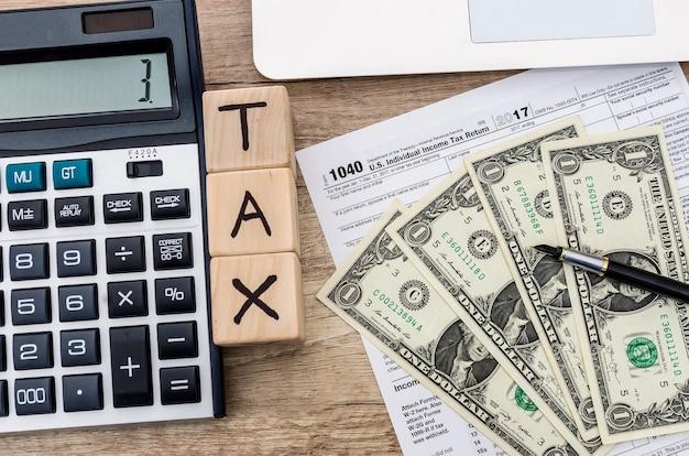 Formulario de impuestos con dólar, calculadora y cubos de madera con texto tax